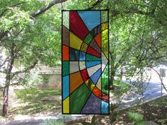 This fun colorful stained glass panel is made with different shades and textures of stained glass in a geometric design.  The panel hangs vertically and has a 1/4 zinc border with the entire panel finished with a black patina.  Measures approximately 10 1/4 x 22 1/2.