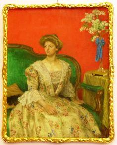 Zasněná dáma v šatech posetých květinami sedící na barokové zelené pohovce s jasně červeným pozadím je Sidonie. Obraz má krásný rám a vůbec je nádherný. Originál obrazu Maxe Švabinského visí na zámku Vrchotovy Janovice