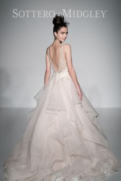 Dione organza creates the dramatic Amelie ball gown with horsehair layered skirt, featuring a breathtaking bodice adorned with Swarovski crystals and pearls, plunging illusion V-neckline and back. Finished with crystal buttons over zipper closure.