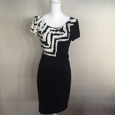 """Max and Cleo black and white geometric print dress Empire waist, cap sleeves with a fitted banded like bottom to dress. Crew neck top. Dress is solid black at the bottom with a zig zag black and white pattern at the top. Fully lined. Nice thick material. Top is 70% polyester 25% rayon 5% spandex. Bottom is 96% polyester 4% spandex. Shoulder to hem 35 1/2"""" Waist 13 1/2"""" Bust 14 1/2"""" Hem 18"""" in perfect condition! Only worn once!! Max & Cleo Dresses Midi"""