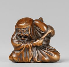 An amusing boxwood netsuke of Daruma disturbed in his meditation, by Gyokusai. 19th century