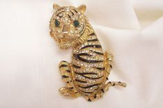 Plaza shop only Memorial 4 day sale 10% off storewide discount taken at purchase or refunded ends 5/28 at midnight. visit my Ruby Lane Shop for more great vintage finds. Shops link on each ones home pages.   Gorgeous green eye and clear pave set Rhinestone Enameled Tiger Brooch