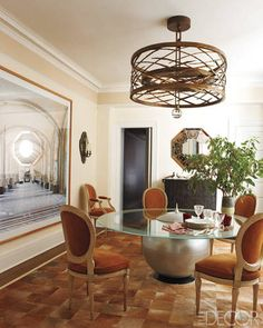 Hervé Van der Straeten's spiral bronze light fixture provides a dynamic focal point in hairstylist Frédéric Fekkai's Manhattan duplex, designed by Robert Couturier. The Louis XVI–style chairs are upholstered in a suede from Edelman Leather, and the large-scale photograph is by Candida Höfer.