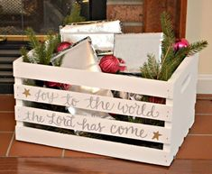 """Blogger Amy wanted to surprise her son with little gifts that would segue into their daily activities. To separate these """"advent gifts"""" from the rest of his Christmas presents, she used a wooden crate dressed up with paint and a festive quote to hold them. For an extra touch of holiday embellishment, Amy added ornaments and pine bough bedding to her crate."""