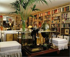 white upholstery, lots of books, and a plant: Yves Saint Laurent Paris apartment.