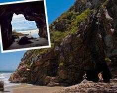Gruta das Encantadas, Paraná, Brasil. A Gruta das Encantadas, na paradisíaca Ilha do Mel, oferece essa linda vista da praia. Ela fica no meio das rochas da Praia de Fora das Encantadas e seu interior é pequeno e com o chão revestido de areia. O acesso é feio por trilha em períodos de maré baixa.