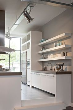 Clean, modern shelving above the fridge.