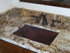 Hammered copper undermount sink with granite vanity.