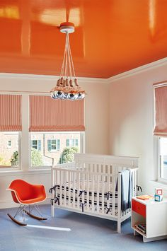 Tan and orange nursery features ceiling painted a glossy orange accented with cluster mercury glass bulbs chandelier hanging over a corner crib dressed in white and navy crib bedding flanked by an orange Eames Molded Plastic Rocker to the left and a two tone table bookcase to the right atop blue carpet tiles alongside windows dressed in orange striped roman shades.