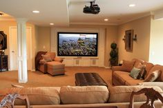 You may never see your family upstairs if the basement is outfitted with comfortable furniture and a high-def projection screen for the ultimate movie-watching experience. Photo courtesy of Finished Basements