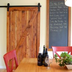 A long chalkboard and sliding barn door bring rustic charm to this dining area. The slate for the chalkboard originally comes from an elementary school and now features the clients' extensive ale collection. The door is made from reclaimed yew wood with no stain and a natural oil finish.