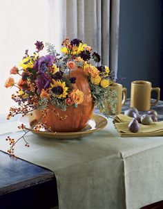 pumpkin-basket floral arrangement how-to. would make a beautiful Thanksgiving table centerpiece.