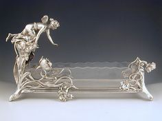 A magnificent Art Nouveau centrepiece with figural maiden reaching into a pond. The frame is silver plate on pewter brass, with crystal glass liner. Country of manufacture Germany (WMF), Image 1 of 2