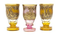 """(lot of 3) Moser glass gilded chalices, each having thick walls, pedestal foot beneath paneled trim, heavily gilded bodies showing figures in a pastoral landscape: (2) signed W. Berndt (Wolfgang Berndt) in amber; (1) pink glass, signed Walter; each approx 6""""h, 4.5lbs **Provenance: From the historic Nelson-Crier house Round Rock, Texas** Start Price: $80.00"""