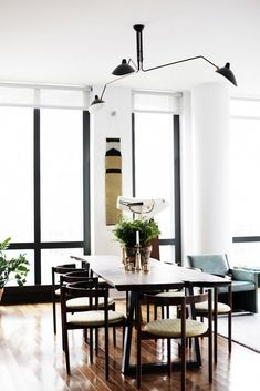 Sputnik light fixture over dining room table with green centerpieces and modern chairs