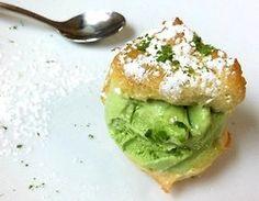 Cream puff stuffed with matcha green tea ice cream, topped with powdered sugar and matcha powder.