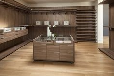 """This spacious closet is of a more minimalist design and has extensive light woodwork throughout. A rolling """"island"""" with a glass top allows you to see into the top divided drawers easily."""