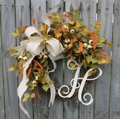 This fall monogram wreath is the perfect harvest time decoration! A gorgeous wired cream ribbon makes an informal bow. The ribbon is wired for easy refluffing from year to year. Realistic orange bean pods, cream crab apples. This wreaths leaves have a light and airy feel where the grapevine base is visible in places. You can enjoy this wreath on your door or in an interior space all autumn long! An antique white monogram provides a lovely accent.  Average Diameter (tip to tip): 21 This…