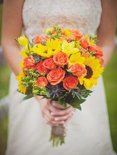 Bride's Bouquet: Blue Eryngium Thistle, Orange Roses, Yellow Freesia, Yellow Sunflowers, Green Hypericum Berries + Green Foliage