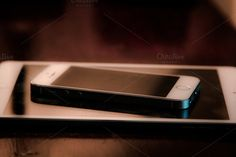 iPhone 5s and iPad mini sitting on a wooden table.