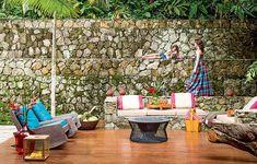 A vocação agregadora da casa de praia está no jardim. Coberto por deque e cercado de mata nativa, o espaço foi coroado com bancos de alvenaria com almofadas, poltronas e uma pira, acesa todas as noites. Projeto da arquiteta Fabiana Avanzi