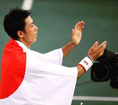 Kei Nishikori drapes himself in a Japan flag after defeating Rafael Nadal to win…