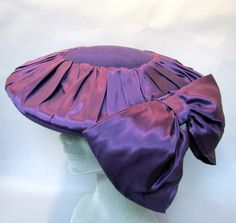 This fantastic hat was made with purple wool and pleated satin in the 1940s. The shape is great with its flat pancake style and large bow that hangs down on the side. This is called an upstanding beret. A wonderful vintage 40s hat that is in great condition! The size measures 22 circumference and is about 14 in diameter. Like this item and looking for more like it? Are you a dealer and want to buy in quantity? Check out our new store on etsy for wholesale vintage purchasing: http:/...