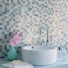 Water world - In this chic bathroom, ice blue glass mosaic tiles cover the countertop and extend into a tiled wall that also includes white and ocean blue.