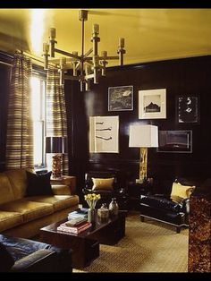 Courageous use of Yellow on Ceiling, combined with Charcoal Walls, Brass, and Black details Create a Dramatic Room.