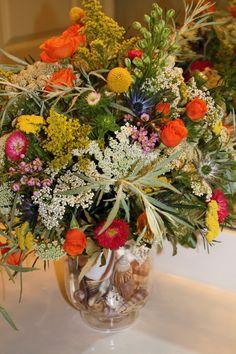 wild flower arrangement in a seashell filled vase
