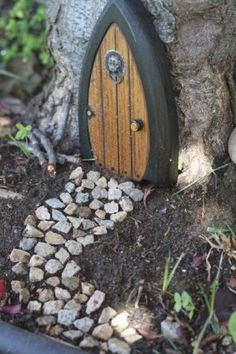 Fairy door and path at the base of a tree trunk ...