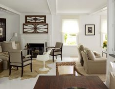 """White walls, ceilings, and floor give the living room of this Southampton, New York, cottage a fresh, light spirit. """"I wanted the house to feel young and fun,"""" says designer Vicente Wolf. He hung antique Indonesian window transoms over the fireplace: """"They're so airy — they don't close up the room."""""""