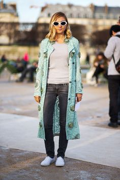 Nasiba Adilova in a patterned mint coloured long coat, jeans, white sneakers. Paris Fashion Week, Street style.