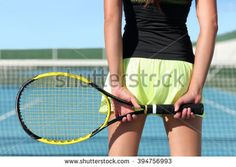 Tennis player holding racket preparing for playing game on outdoor court during summer. Closeup of hands and sport skirt with net in the background. Unrecognizable lower body of person from the back. - stock photo