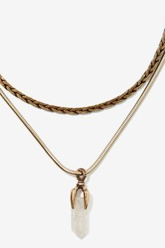 Play by your own rules. The Bend the Claw Necklace features a small silver snake chain, dark gold layered braided chain, gold claw pendant holding a clear crystal
