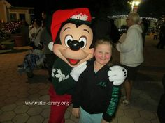 Ali with Mickey Mouse at the Give Kids The World Christmas celebration.