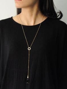 Coachella Necklace in Black -  INR 1,199 - This Lariat necklace features a Gold metallic finish and a long chain link drop. This necklace is fresh on trend and looks great layered with a plunging neckline or on its own. The bottom of the link drop features a ombré Black beaded tassel that adds a perfect pop of sheen.