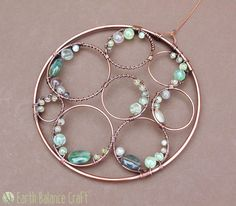 Handmade copper wire work ocean crest suncatcher with watery gemstones.