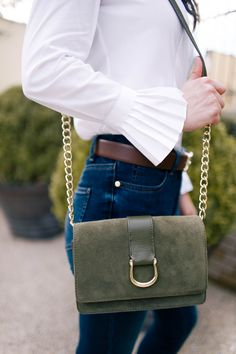 Classic white shirt with pleated cuffs and horsebit crossbody bag.