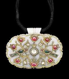 A Mughal gem-set gold mounted jade Pendant (Haldili)   India, late 18th/early 19th Century  cartouche-shaped, inlaid with gold and set with cabochon-cut rubies and emeralds and tablet-cut diamonds in a three-stemmed symmetrical floral motif emanating from a small oval ruby, with two birds in profile flanking the central diamond, drilled for suspension   5.2cm wide