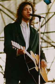 Bob Geldof, a Caucasian man in his mid-thirties, is on stage, singing into a microphone and playing a left-handed acoustic guitar. He wears a white shirt and a dark green jacket. Ska Music, Music Icon, Brenda Ann Spencer, Left Handed Acoustic Guitar, Bob Geldof, The Jam Band, Star Wars, Pop Rock Bands, We Are The World