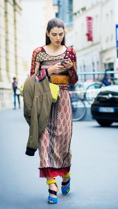 A patchwork-print midi dress is worn with a bomber jacket, bright bag, and colorful Prada heels