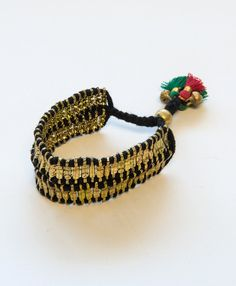 Black thread is entwined with unique brass beads and finished with a brightly colored tassel. Fully adjustable, this bracelet is sure to be a perfect fit!