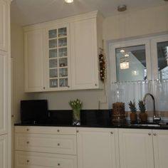 Delikatnie stylizowane fronty w jasnym kolorze, przeszklenia, pilastry, dekoracyjny gzyms i czarny granitowy blat - recepta na ponadczasową kuchnię w stylu klasycznym.