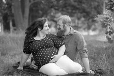 Expecting mother, holding baby bump, looking at each other lovingly, sitting on blanket in field near fence with husband during family maternity photography session by Kasey Wallace Photography in Corunna, Indiana, black and white photograph, www.kaseywallacephoto.com