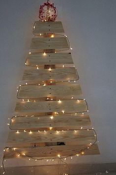 Vous avez des palettes et une guirlande lumineuse, fabriquez votre sapin de Noël artificiel. Ambiance zen assurée !