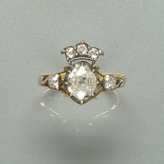 A diamond dress ring, first quarter of the 19th century The central old brilliant-cut diamond set within a closed-back pinched collet mount, surmounted by a diamond-set coronet motif, to trifurcated shoulders with scrolled detail, each set with a further old brilliant-cut diamond, principal diamond approx. 1.10ct.