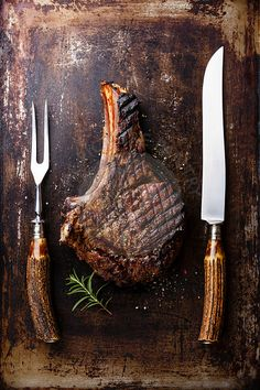 Grilled Ribeye Steak on bone and fork and knife carving set on old scratched dark background