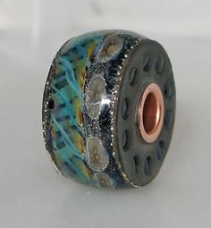 Sewing bobbin filled with glass and cored in copper.