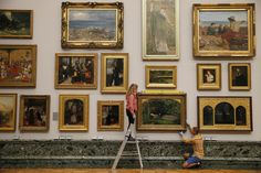 """Tate staff pose with the painting """"Ophelia"""" by John Everett Millais at the Tate Modern in London August 7, 2014. The painting returns home to Tate Britain following an international tour. REUTERS/Stefan Wermuth"""